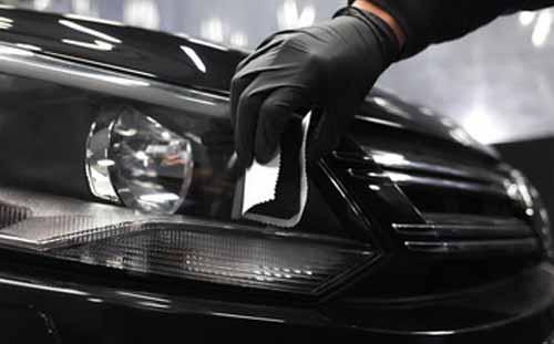 fényszóró polírozása egy fekete autón demonstrálva